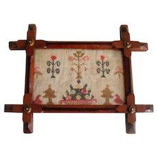 Small antique sampler in cross frame