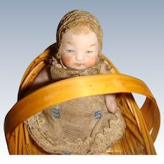 All bisque baby doll in basket well dressed