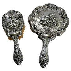 Two piece Victorian sterling silver dresser set with cupid decoration made by Gorham Company