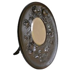 Oval bronze frame with beveled glass and rose and leaf relief decoration