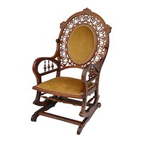 Oak platform rocker with unique open carved design around an oval upholstered back