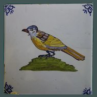 Old Dutch Tile-bright  Bird perched on a knoll