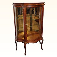 Oak curio cabinet with serpentine glass c. 1890s