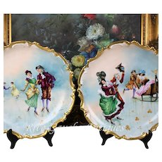 """Rare pair of 13.5'' Limoges France hand-painted plats/ chargers decorated the skating couples, artist signed """"Banazan"""", 1920s"""