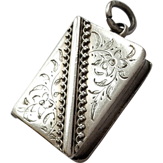 Antique silver pendant locket designed to look like a book