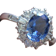 Traditional Vintage oval sapphire ring surrounded by diamonds set in platinum