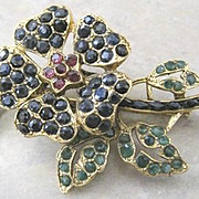 Swoboda Floral pin by Nate Waxman set with rubies, sapphires and emeralds in a gold plated base