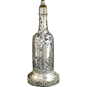 Floral Coin Silver overlay on a glass bottle made into a lamp