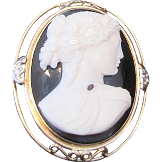Carved white stone cameo set on black onyx with 14kyg pin bezel and diamonds