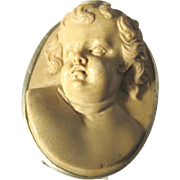 Victorian Italian Lava cameo of a baby boy set in a  silver frame with a pin and hook closure