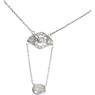 Ladies Platinum and 0.64 oval Diamond dangle necklace with stations of 0.18tw diamonds on the chain