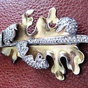 Deja gold washed rhinestone curled leaf pin