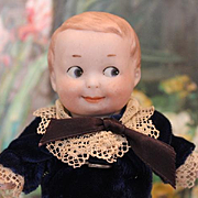 "Armand Marseille, German Antique AM Googly, Googlie bisque head, Boy doll, composition body, hands, legs. Sewn on clothes, velvet and lace outfit, marked head. 6 1/4"" tall."