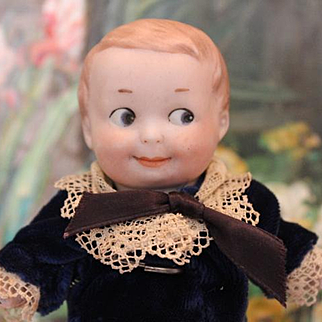 """Armand Marseille, German Antique AM Googly, Googlie bisque head, Boy doll, composition body, hands, legs. Sewn on clothes, velvet and lace outfit, marked head. 6 1/4"""" tall."""