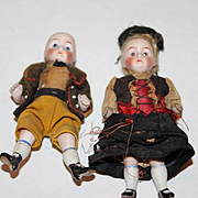 "Brother and sister all bisque German antique dolls. wire attached arms and legs. 4 1/4"" tall, old clothes,  painted socks and shoes, clothes are sewn on."