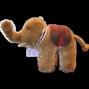"""Vintage late 1956-1976's  Steiff Tiny Elephant,  Never produced with tag. Missing one ear. White plastic tusks, tan felt ear, black button eyes. 3"""" tall X 3 3/4"""" long.  Mohair Steiff animal."""