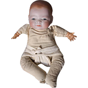 "German Bye Lo baby with  2 hairlines, on top of bisque head, original frog style cloth body, hard plastic hands, comes in diaper as shown. 11"" long in size. 3 spots on top of head."