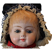 "16 1/2"" tall Antique Papier, Paper Mache doll, original blond mohair wig, antique  print cotton dress with lace at the neck and sleeves.  Blue glass eyes, Oilcloth doll body."