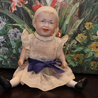 """Antique German Recknagel doll, 8"""" tall, bisque head with molded hat, big smile, wearing a dress, composition body. Made in Germany  1886 and on."""