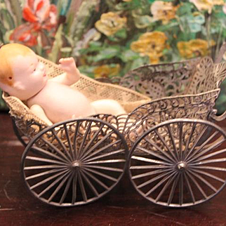 Bisque baby with 2 faces, happy and mad look, in antique metal doll carriage!  Swivel head doll. Marked Germany