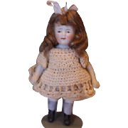 """Cute little 4 1/2"""" tall all bisque girl doll with  nice brown mohair wig, cute beige crochet dress and pantaloons, unmarked. closed mouth doll."""