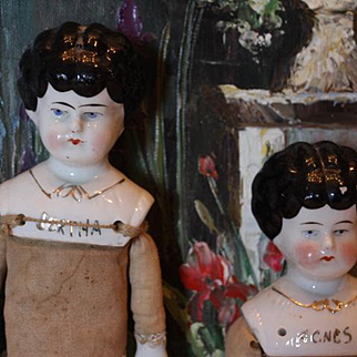 """Pair of china head dolls, Agnes and Bertha shoulderhead dolls. Flag body and cloth & leather body. China arms on them. 12 1/4"""" tall and 9 1/2"""" tall."""