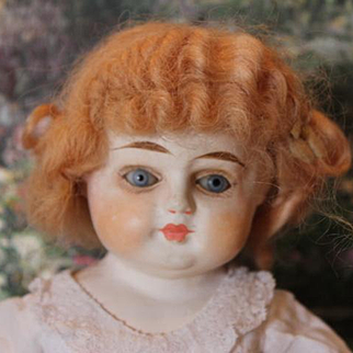 """Antique Small 12"""" Papier Mache Shoulder head doll on new cloth body with papier mache arms. Wig is strawberry blond color. Dress has holes."""