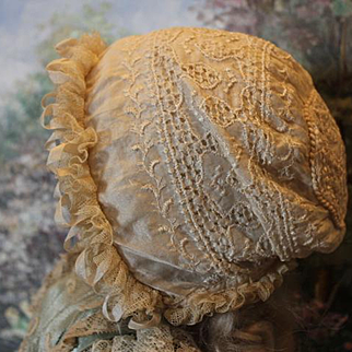 "Nice Antique all Silk and antique lace doll bonnet. Silk lining with no holes. Embroidered silk fabric. No tie strings. 6"" X 5 1/2"" folded flat in size."