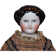 """All original beautiful  glazed China Head doll, German Antique doll, antique clothes, layers of slips, leather sewn on boots, crack on shoulderhead. 16"""" tall in size."""