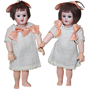 "Pair of Twins! Bisque Head Armand Marseille on composition bodies. 6 1/2"" tall in size. Marked Germany and AM. One has sleep eyes. Open mouth teeth."