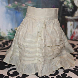"""Antique doll slip, stiff cotton organdy type fabric. Pleated and gathered. Button closure. 5 1/4"""" long X 10"""" wide at bottom. Waist is about 7 1/2"""" around."""