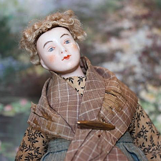 """Unusual Dressel and Kister China head doll, bisque hands, china head, wired stuffed body. 11 1/2"""" tall. damage on lower leg."""