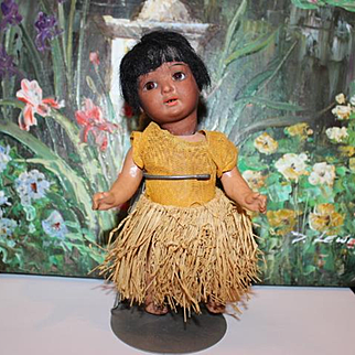 """Schoenau & Hoffmeister German Antique doll, Character Hanna doll dressed as an Island Girl! Grass skirt and and cloth dress, mohair wig, sleep  eyes. 7"""" tall in size."""