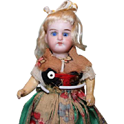"""5 3/4"""" tall bisque head doll, black bisque painted legs. compo arms. Problem with one leg! Marked Germany 15.0, blue glass set eyes, original costume."""