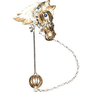 Equestrian 18K yellow and white gold horse head brooch set with diamonds and sapphire.