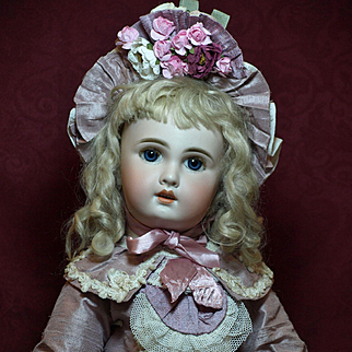 A Sweet Jumeau Bebe (size 10) with Sparkling Blue Glass Paperweight Eyes and Mohair Lashes - Wearing a Lovely Couture Dress- Matching Bonnet and Antique Shoes with Rosettes