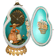 Vintage Teal colored Egg box with a wood doll inside doing gardening.
