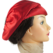 BONWIT TELLER red satin hat with rhinestone accent.