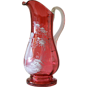 An antique  cranberry ' Mary Gregory ' glass jug depicting a girl in a garden, 1900c.