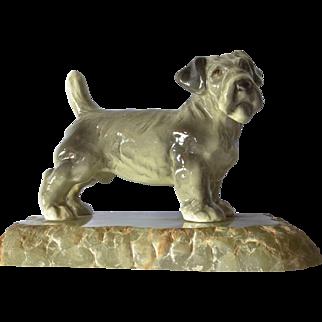 A porelain terrier dog on a stone base, 1900c.