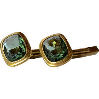 A vintage pair of brass cufflinks with green glass stones.