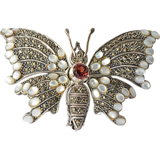 A silver mounted butterfly brooch set with marcasite, mother of pearl and a single garnet,1940c.