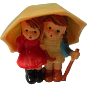 Early Plastic Figure of 2 Children Under Umbrella