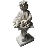 All Bisque Figurine of Boy Holding Tray on His Knee