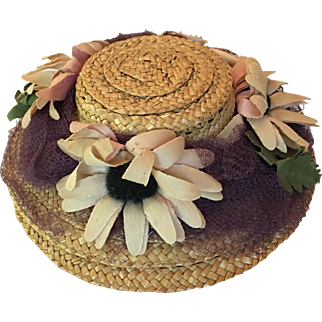 Straw hat with fabric flowers, netting, and ribbon