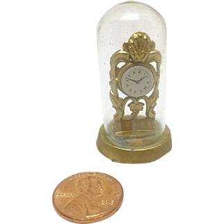 Miniature gilded clock in glass dome