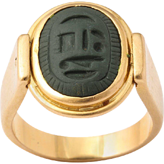 An intriguing ring that artistically set, with an  oval scarab that rotates.  On one side is the scarab and when rotated, th