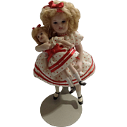 Miniature Porcelain Shirley Temple Doll Holding a Shirley Temple Doll In Red Polka Dot Dress and Black Shoes