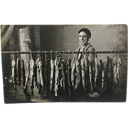RPPC, fishing 1910's, a day's catch of pike, painted backdrop.