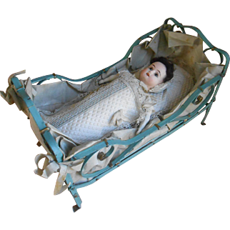 **An iron French small doll's bed with a swaddled doll...all original***